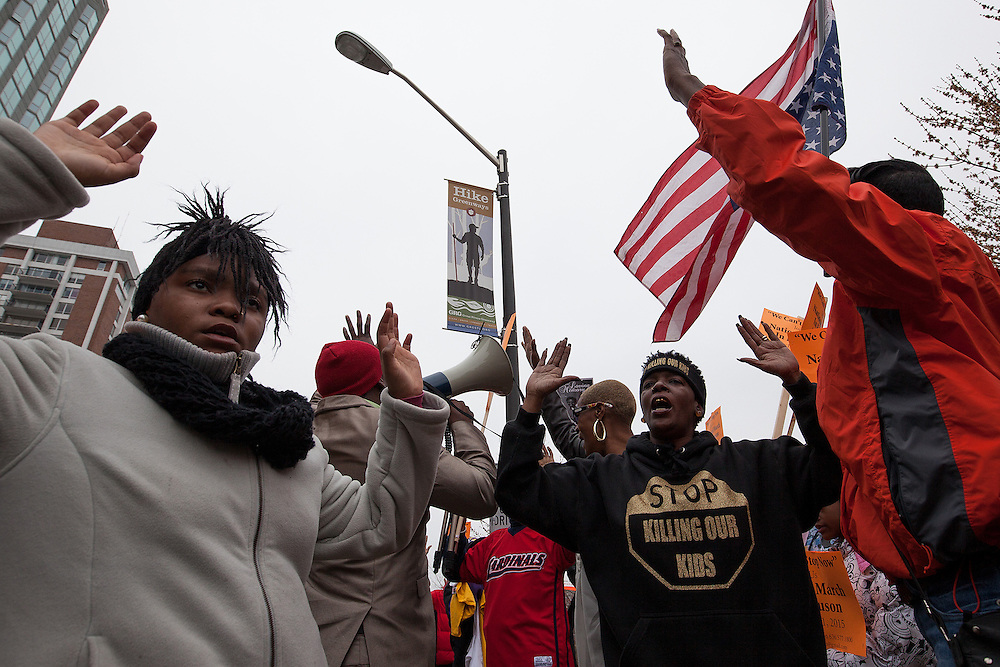 "Protesters raise their arms in unison while chanting ""Hands up, Don't shoot"" during a march through the streets of Clayton, Missouri."