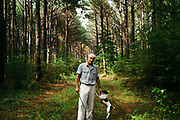 "MERIDIAN, MS – AUGUST 3, 2018: Clayton George, 57, walks under a canopy of mature Loblolly pine with his dog, Poupon. As a resident of Tennessee, George makes the four hour drive south every two weeks to check on his family's 400 acre tract, and visit his father who still lives there.<br /> <br /> In 1987, George and a friend walked in rows planting the family's first batch of Loblolly pine, where soybeans, wheat and cattle once covered the family's 400 acres.  The shift to timber was largely prompted by the Conservation Reserve Program, a popular new farm subsidy in the 1980s that encouraged farmers to reforest depleted land by paying them for every acre of trees planted. Since 1926, the George family had made a good living from their eastern Mississippi farm, but the decline of soybeans and other crops eventually led George to consider growing trees instead – a crop that landowners throughout the south believed would bring in easy money. Thirty years later, however, the same landowners are now facing unexpected financial hardship. Stumpage prices have been on a steady decline – as much as 45% since 2007 – and landowners are rethinking timber as a worthwhile investment. """"We figured we''d plant trees and come back and harvest it in 30 years, and in the meantime go into town to make a living doing something else,"" George said. As co-owner of the family acreage with three other family members, George always considered himself the most nostalgic Now, as he patiently awaits for right time to harvest a 30 year investment, even he considers the future of the land uncertain. CREDIT: Bob Miller for The Wall Street Journal<br /> TIMBER_AL"