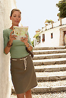 Tourist standing on steps reading map in Granada Spain front view