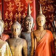 Buddha statues at Wat Xieng Thong (Temple of the Golden City) on the northern tip of the peninsula of Luang Prabang, Laos. Originally built around 1560, the temple was the main site for royal coronations and remains ones of the most important temples in Laos.