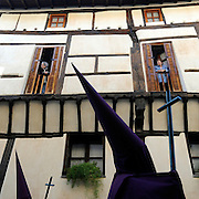 Two women look at penitentes as they parade during the Maundy Thursday procession on April 17, 2014 in the northern Spanish Basque village of Segura.   PHOTO/ RAFA RIVAS