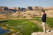 Bob Sorensen, an assistant golf course superintendent of The Golf Club at Redlands Mesa in Grand Junction, Colorado stands at a vantage point during a routine inspection of the golf course. (Bob Sorensen is featured in the book What I Eat: Around the World in 80 Diets.) He played football at Mesa State College in Grand Junction and graduated with a degree in criminal justice. Just before he took a desk job in his chosen profession he decided that he didn't want a desk job and found one that requires his constant attendance of the great outdoors, at a golf course at the foot of the majestic Colorado National Monument. Some of his work is physical, but technology makes his irrigation chores easier. From one of many rock outcrops overlooking the lush fairways and greens in the dry, high desert valley, he can control a matrix of sprinklers with a single radio controller.  He earned a second degree in turf management, supervises a small crew of greenskeepers, and coaches high school football at Palisade High School.