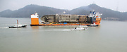 South Korea's Coast Guard vessels escort semi-submersible ship Dockwise White Marlin carrying Sewol Ferry en route to Mokpo New Port in Mokpo, about 311 km (193 miles) south of Seoul, South Korea, Mar 31, 2017. The Sewol Ferry sailed into the port on Friday, about three years after it sank off South Korea's southwestern coast near Jindo on April 16, 2014 during a journey from Incheon to Jeju. The Ferry was carrying 475 crew and passengers, mostly high school students on a school trip. More than 300 people died and nine are still missing. Authorities will search for the bodies of nine missing and look into the wreck to find cause of the sinking. The Sewol was built in Japan in 1994 and it was decommissioned ship already when South Korea imported it from Japan in late 2012. South Korean government led by at the time President Lee Myung-Bak increased the maximum ship age from 20 to 30 years in 2009 as part of a drive to relax regulations, local media reported. Photo by Lee Jae-Won (SOUTH KOREA) www.leejaewonpix.com