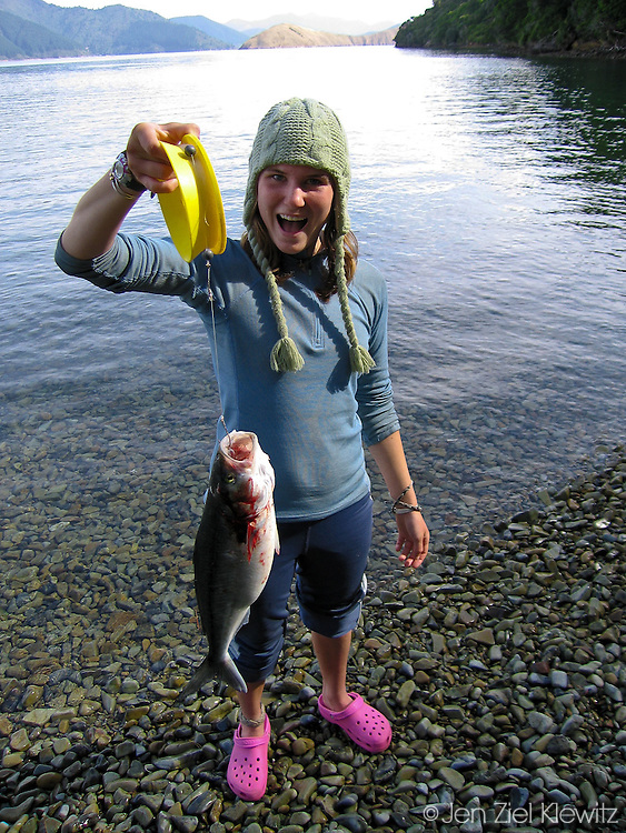 A student delights at her catch while camped in the Marlborough Sounds of New Zealand during a Sea Kayak Section of a Semester course with the National Outdoor Leadership School. Photo by Jen Klewitz © 2008