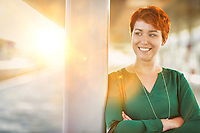 Portrait of smiling confident businesswoman standing with arms crossed
