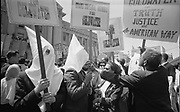 Ku Klux Klan members supporting Barry Goldwater's campaign for the presidential nomination at the Republican National Convention, San Francisco, California, as an African American man pushes signs back: 12 July 1964.  Photographer:  Warren K  Leffler.