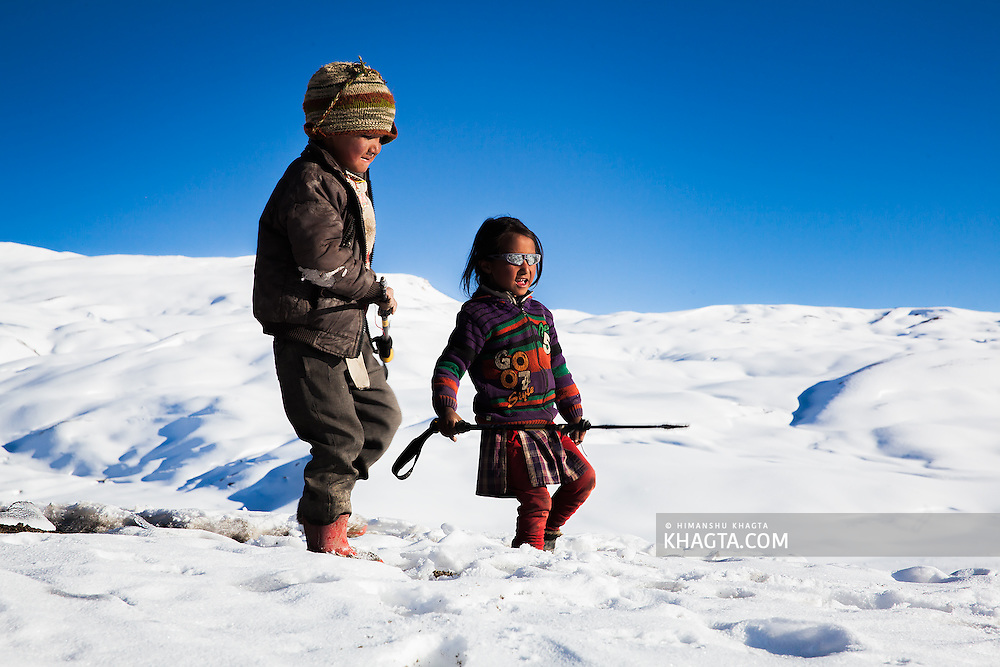 Kids of the high altitude villgae of  Langza, at an altitude of 14300ft,  walks together in snow covered terrain.