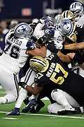 Dallas Cowboys running back Ezekiel Elliott (21) gets gang tackled by New Orleans Saints defensive end Alex Okafor (57) and Saints teammates on a third quarter run good for a first down during the NFL week 13 regular season football game against the New Orleans Saints on Thursday, Nov. 29, 2018 in Arlington, Tex. The Cowboys won the game 13-10. (©Paul Anthony Spinelli)