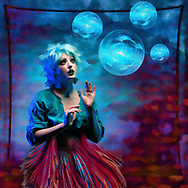 Colorful surreal image of a model gazing at bubbles with a fish tail skirt against a red and blue background