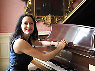 Old Westbury, New York, USA. December 17, 2017. Pianist Angelina plays Christmas music on Steinway grand piano to entertain visitors at Old Westbury Gardens museum, a former estate of John Shaffer Phipps, during snowy winter holiday weekend.