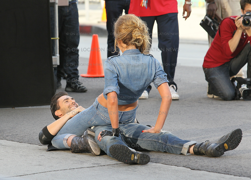 "May 14th 2010. Los Angeles, CA. ***EXCLUSIVE*** Adam Levine and his beautiful Russian Supermodel girlfriend Anne Vyalitsyna filming a Maroon 5 Music Video for their song ""Misery"". The sexy couple filmed various scenes of loving affection with passionate kissing followed by scenes of humorous violence and destruction. In this action packed Music Video shot on the streets of Downtown Los Angeles, Adam Levine and his band mates are fleeing from Anne Vyalitsyna who is humorously trying to kill them in various ways. Scenes include a missile gun attack and knife throwing from Anne, Adam being hit by a car while running away, Adam being close lined by Anne off a motorcycle that he is fleeing on,  Adam being kicked through a cafe window as well as being ejected from the window of a high rise building. The couple were constantly kissing, hugging and holding hands while on set. They both shared a big luxury trailer while not filming. Photo by Eric Ford/ On Location News. 818-613-3955. info@onlocationnews.com"