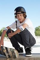 Teenage boy (16-17) with skateboard at skateboard park portrait