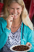 Andrea Johnson eating grasshoppers, specialty of Son La village, northern Vietnam