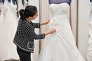 Side view of mature woman adjusting bridal dress in boutique