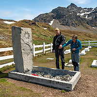 Naturalists Andreas Madsen and Karen Velas pour whisky onto Sir Ernest Shackleton's as a toast. Shackleton's grave is in the cemetery near the old whaling station at Grytviken on the north coast of South Georgia Island.