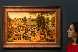 "© Licensed to London News Pictures. 02/12/2016. London, UK. A staff member views ""Return of the Kermesse"" by Pieter Breughel the Younger (est. GBP 2-3m), at a preview of Sotheby's upcoming Old Masters Evening Sale in New Bond Street. Photo credit : Stephen Chung/LNP"