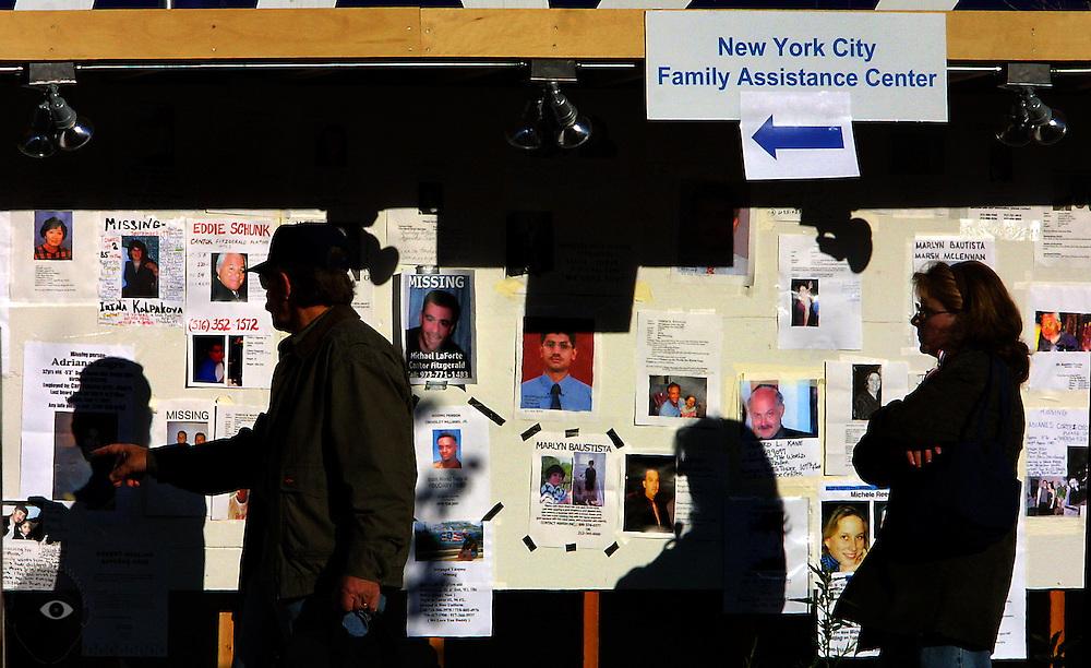 People stop to notice one of the many missing person postings outside of the New York Family Assistance Center.