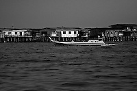 stilt houses and fishing boat off the coast of sandakan, borneo