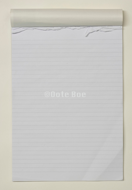 Still life of a used lined notepad open on an empty page