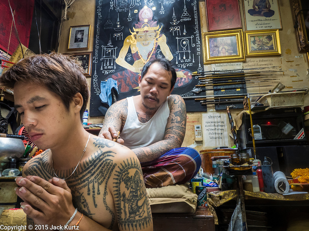 "27 MAY 2015 - BANGKOK, THAILAND: AJARN NENG ONNUT, blesses the tattoos of a Thai man who came to Ajarn Neng's home. Ajarn Neng is a revered master of sacred tattoos and sees people all day at his Bangkok home. Sak Yant (Thai for ""tattoos of mystical drawings"" sak=tattoo, yantra=mystical drawing) tattoos are popular throughout Thailand, Cambodia, Laos and Myanmar. The tattoos are believed to impart magical powers to the people who have them. People get the tattoos to address specific needs. For example, a business person would get a tattoo to make his business successful, and a soldier would get a tattoo to help him in battle. The tattoos are blessed by monks or people who have magical powers. Ajarn Neng, a revered tattoo master in Bangkok, uses stainless steel needles to tattoo, other tattoo masters use bamboo needles. The tattoos are growing in popularity with tourists, but Thai religious leaders try to discourage tattoo masters from giving tourists tattoos for ornamental reasons.     PHOTO BY JACK KURTZ"