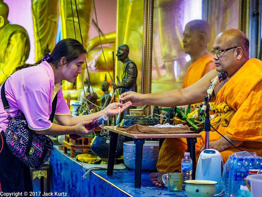 """24 JUNE 2017 - BANG KRUAI, NONTHABURI: A Buddhist monk gives a prayer bracelet to a woman after a rebirthing ceremony at Wat Ta Kien (also spelled Wat Tahkian), a Buddhist temple in the suburbs of Bangkok. People go to the temple to participate in a """"Resurrection Ceremony."""" Thai Buddhists believe that connecting people by strings around their heads, which are connected to a web of strings suspended from the ceiling, amplifies the power of the prayer. Groups of people meet and pray with the temple's Buddhist monks. Then they lie in coffins, the monks pull a pink sheet over them, symbolizing their ritualistic death. The sheet is then pulled back, and people sit up in the coffin, symbolizing their ritualist rebirth. The ceremony is supposed to expunge bad karma and bad luck from a person's life and also get people used to the idea of the inevitability of death. Most times, one person lays in one coffin, but there is family sized coffin that can accommodate up to six people. The temple has been doing the resurrection ceremonies for about nine years.     PHOTO BY JACK KURTZ"""