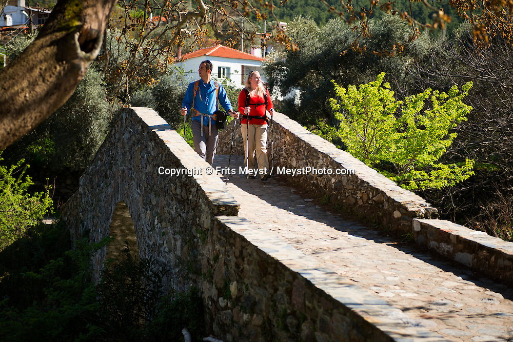 Mugla, Turkey, March 2014. Hikers on a bridge in the village of Gevenes, better known by Turks for its Belen Kahvesi on the Carian Trail section from Belen Kahvesi to Stratonikeia. The Carian Trail runs through pine scented forests along the coastal mountains of Western Turkey and is littered with ancient ruins, secluded coves with turquoise waters and little villages. more than 800km of ancient roads, shepherd paths and forest trails form Turkey's longest hiking trail.  Photo by Frits Meyst / MeystPhoto.com