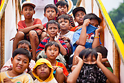 Apr. 25 -- UBUD, BALI, INDONESIA:   Children watch the cremation of Cokorde Gede Raka, a member of Ubud's royal family, Sunday, Apr. 25. Balinese are Hindus and cremate their dead. Balinese funerals are elaborate - and expensive - affairs. A funeral for one person costs a minimum of 45 million rupiah (about $5,000 US). The body is placed into the bull's body at the cremation and cremated in the bull. The funeral pyre is burnt adjacent to the bull. That is what a family may earn in two to three years. The result is that only the rich can afford formal cremations. The body (in the casket) is placed in the top of the funeral pyre and the procession takes the body to the cremation site. The funeral pyre, and the body, are spun at intersections to confuse the spirits so the soul doesn't try to return to its home and to confuse evil spirits.    PHOTO BY JACK KURTZ