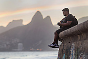 A man plays guitar on the seawall at Ipanema beach during sunset with the Two Brother mountains in the distance in Rio de Janeiro, Brazil.