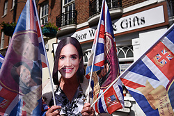 © Licensed to London News Pictures. 18/05/2018. LONDON, UK.  A souvenir wears a Meghan Markle mask as preparations in Windsor for the wedding between Prince Harry and Meghan Markle on 19 May continue.  Tens of thousands of people are expected to visit the town for what has been billed as the wedding of the year. Photo credit: Stephen Chung/LNP