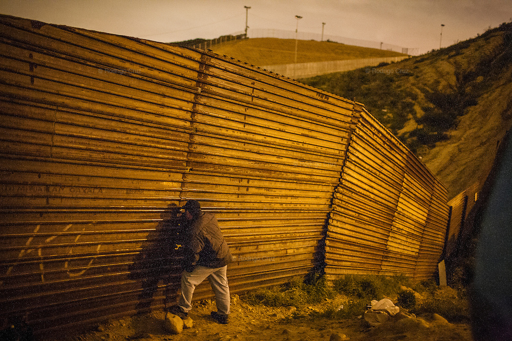 A man watches through a hole the movements of the U.S. Border Patrol and overnight waits patiently for the right moment to jump up the wall that separates Mexico from the United States, on November 11, 2009 in Tijuana, Mexico.