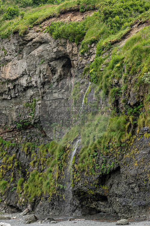 A small waterfall cascades down the rock cliffs along the Cook Inlet at the remote McNeil River Game Sanctuary in the Katmai Peninsula, Alaska. The remote park has the largest concentration of brown bears in the world.