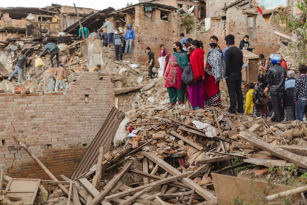 Neighbours from homes that were destroyed during the 2015 Nepal earthquake search for survivors and salvage belongings from the rubble.