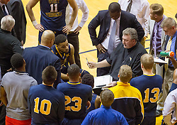 West Virginia Mountaineers head coach Bob Huggins talks to his team during a timeout against the Oklahoma State Cowboys during the second half at the WVU Coliseum.