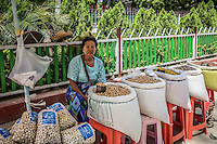 Woman mans her stall selling a range of dried beans and grains in Mingun, near Mandalay, Burma