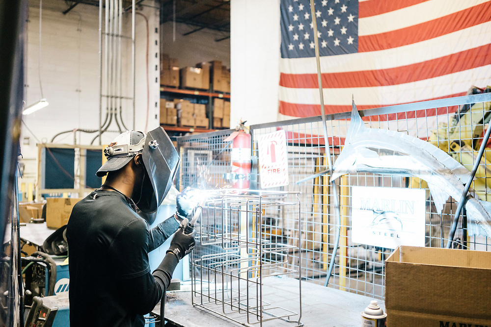 Malcolm McCraw works on constructing Dolby 3D glass holders at Marlin Steel Wire Products LLC in Baltimore on March 16, 2017. Marlin Steel uses three robots on their production floor, one from Ready Robotics, a company less than two miles away. CREDIT: Greg Kahn / GRAIN for the Wall Street Journal ROBOTGAP