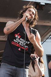 """© Licensed to London News Pictures. 21/06/2014. London, England. Actor, comedian and political campaigner Russell Brand speaks at the No More Austerity demonstration and festival in Parliament Square, London. The event was organised by the People's Assembly. He stripped and put on a shirt with the Spanish firefighters' slogan """"We rescue people, not banks!"""" Photo credit: Bettina Strenske/LNP"""