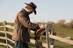 cowboy putting a saddle on a fence