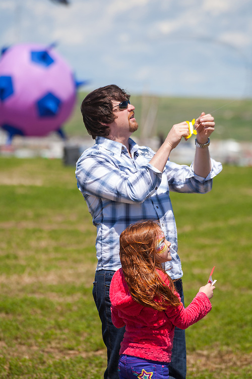 Terence Côté, from Coronach, Saskatchewan, and a friend of his daughter fly a kit. Terence saw a poster promoting the festival at his local library and decided to take his daughter and friends to the festival for the weekend to celebrate her birthday. Windscape Kite Festival, Swift Current, Saskatchewan.