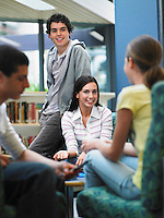 Group of teenagers talking in library