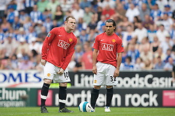 WIGAN, ENGLAND - Sunday, May 11, 2008: Manchester United's Wayne Rooney re-adjusts himself before the final Premiership match of the season against Wigan Athletic as team-mate Carlos Tevez look on at the JJB Stadium. (Photo by David Rawcliffe/Propaganda)