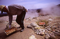 An egg seller takes out a basket of steaming eggs on the slopes of volcanic Mt Iozan in eastern Hokkaido