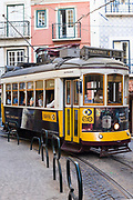 Historic famous number 28 tram carrying local people and tourists on tram tracks along narrow street in Alfama District, Lisbon, Portugal