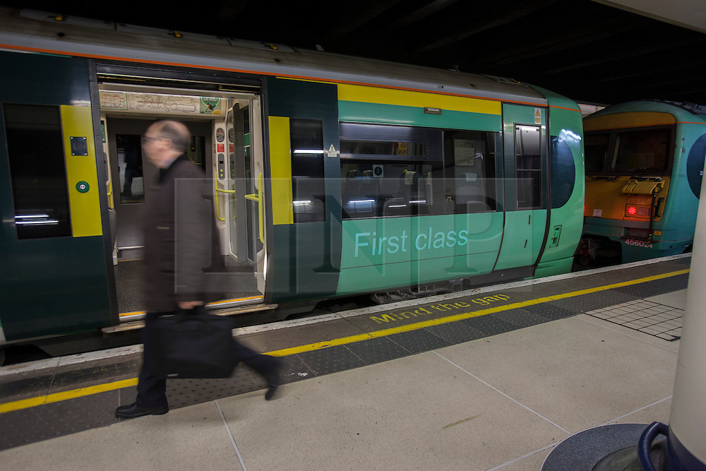 © under license to London News Pictures. 02/01/14. An average 2.8% increase in rail fares comes into effect on Thursday 2nd Jan 2014, pushing the cost of some commuter travel to more than £5,000 a year. FILE PICTURE DATED: 28/11/2012. A passenger walking to a train at Victoria Train Station. Rail fares set to increase by an average of 4.2% in January, a watchdog has revealed. Photo credit: Tolga Akmen/LNP