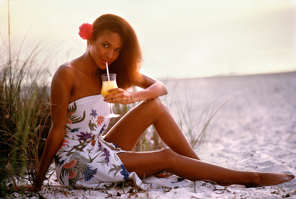 Young dark skinned woman sitting on the beach with the ocean in the background waring a colorful sun-dress sipping a tropical drink.