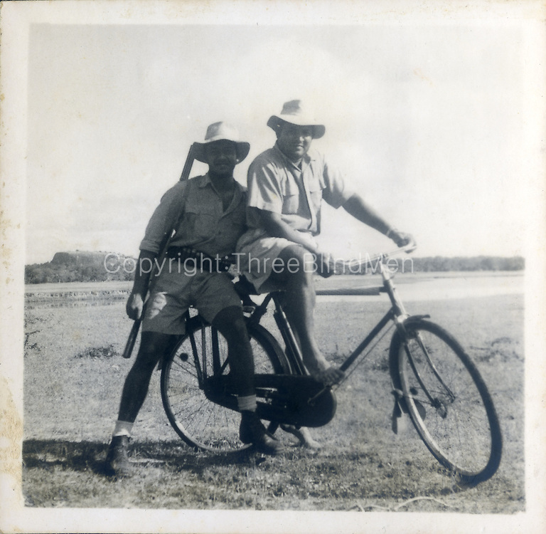 """On the cycle seat Lance Fernando & behind, myself—bagura nov 53. The bike belonged to the Wild life dept tracker Galappatty  --he was stationed at Okanda & used the bike on the jungle tracks."""