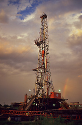 Dramatic post-storm sky with rainbow surround an on-shore Texas oil drilling rig.