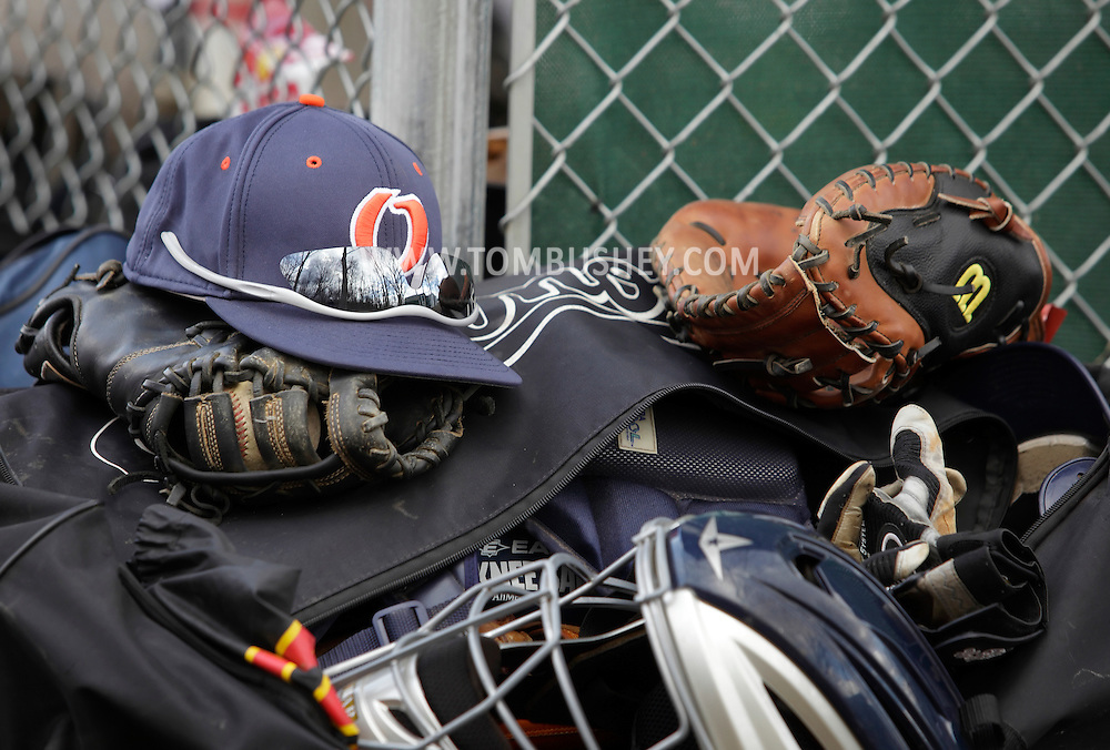 Middletown, New York - Baseball equipment, including hats and gloves, is piled up behind the dugout during a junior college baseball game on April 2, 2011.s