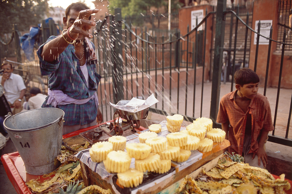 A vendor sprinkles water on his pineapples to keep them fresh in the sumer heat. Old Delhi, May 2006