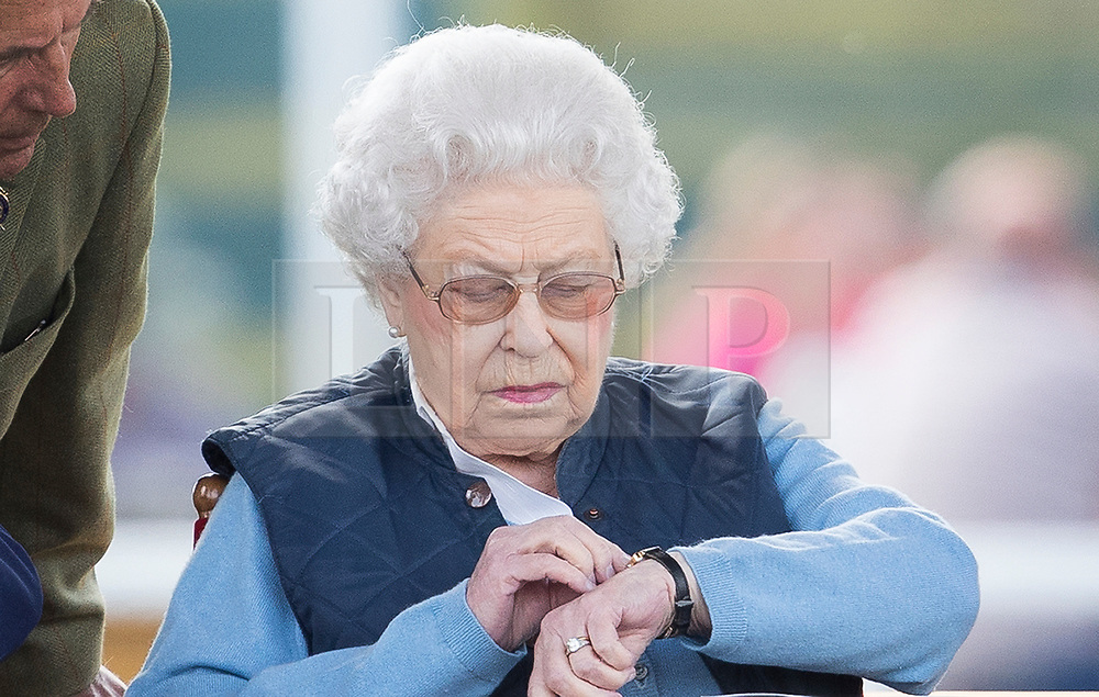 © Licensed to London News Pictures. 09/05/2018. Windsor, UK. Queen Elizabeth II checks the time as she watches her horse 'Sparkles' in competition at the 75th Royal Windsor Horse Show . The five day event takes place in the grounds of Windsor Castle. The Queen and the Duke of Edinburgh usually attend. Photo credit: Peter Macdiarmid/LNP