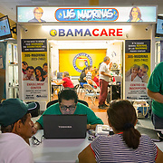 MIAMI, FLORIDA, NOVEMBER 16, 2016<br /> Rudy Figueroa, center, a licensed insurance agent, looks at a computer as he helps two customers at the mall kiosk of Sunshine Health and Life Advisors inside the Mall of the Americas in Miami Dade County. Customers have expressed concerns about &quot;Obama Care&quot; following the election of Donald Trump in the recent presidential elections.<br /> (Photo by Angel Valentin/Freelance)